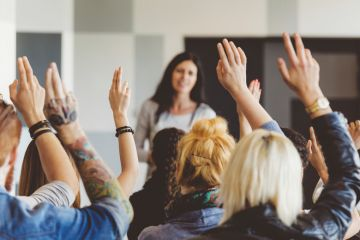 Students raising hands during lecture