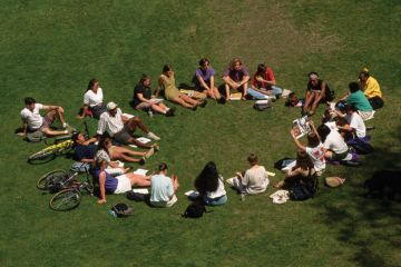 Students sitting in circle outside on lawn