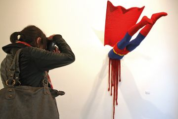 Artwork showing a superhero crashed into a wall