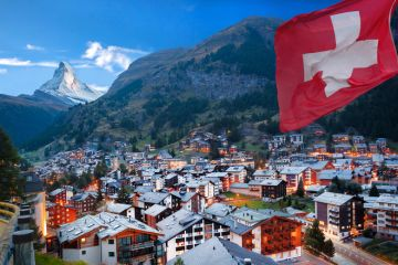 Swiss town with flag of Switzerland and Swiss Alps (Matterhorn) in background