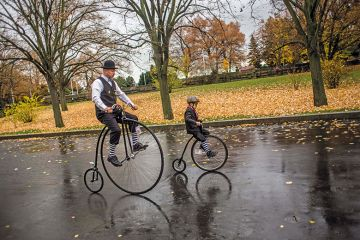 child rides past adult on high-wheel bicycles