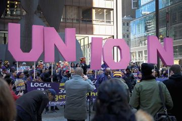 Members of the Service Employees International Union hold a rally in support of the American Federation of State County and Municipal Employees union