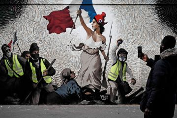 """A man takes a picture of a mural by street artist PBOY depicting Yellow Vest (gilets jaunes) protestors inspired by """"La Liberte guidant le Peuple"""" painting by Eugene Delacroix in Paris on January 8, 2019"""