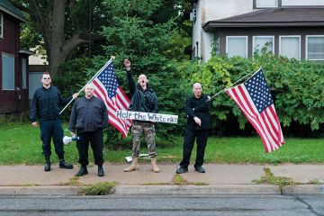 Neo-nazis holding American flag. White supremacists