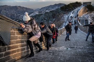 A Chinese tourist uses the scarf of a friend as she is helped while she and others  struggle to climb in the wind on an icy section of the Great Wall at Badaling, on a cold day after a snowfall