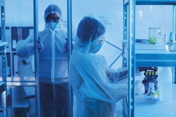 male medical scientist in protective workwear opening door to laboratory room