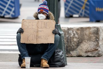 """A homeless person wearing gloves and a protective mask sits with a sign that reads, """"Seeking Human Kindness"""" amid the coronavirus pandemic on April 19, 2020 in New York City, United States."""