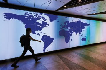 Person walking past map of the world