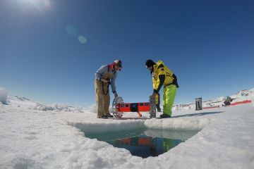 Kevin Hand and Dan Berisford prepare to deploy their under-ice roving robot (BRUIE) through a hole in the sea ice in Antarctica