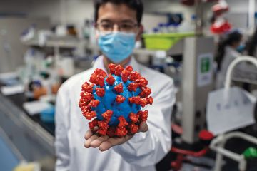Scientist with model of coronavirus