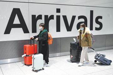 Chinese passengers wear face masks as the push their luggage after arriving from a flight at Terminal 5 of London Heathrow Airport