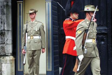 A member of Australia's Federation Guard mans the sentry box with two other guards marching away, one also an Australia's Federation Guard the other a British Grenadier Guard, as a metaphor for Australian institutions changing guard.