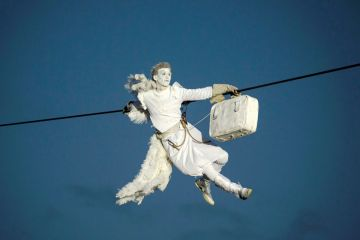 A performer is suspended from high-wires during the outdoor aerial performance of  a show