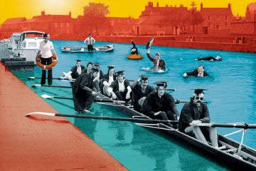 Graduates in rowing boat with people in suits in the water