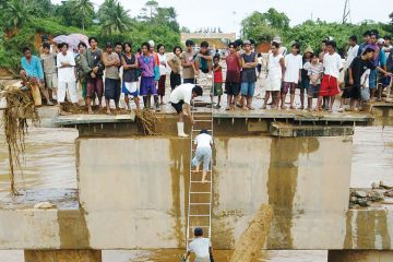 Villagers use an aluminium ladder to cross a concrete bridge as a metaphor for Is South-east Asia  higher education's next global hotspot