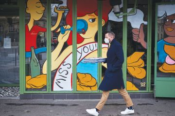 Image of a man swalking past a closed restaurant with a miss you illustration on the shop window