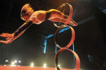 Girl jumps threw hoop at circus