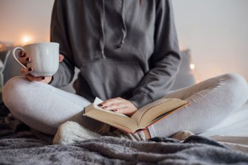Woman reading book and drinking tea on bed