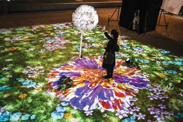A woman uses her smartphone in an interactive multimedia installation that connects Singapore and Japan in a time of separation, in Tokyo on November 13, 2020