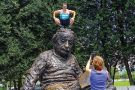 Man squatting on Albert Einstein memorial statue