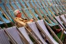 Elderly man sitting alone in rows of deckchairs