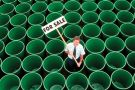 Man standing in rows of green plastic water butts, holding 'For sale' sign