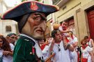 A child react (R) as Caravinagre 'Vinegar face' kiliki (C) approaches during the Comparsa de Gigantes y Cabezudos, or Giants and Big Heads parade on the third day of the San Fermin Running of the Bulls festival on July 8, 2016 in Pamplona, Spain.