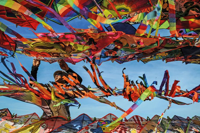 A man surrounded by colourful kites