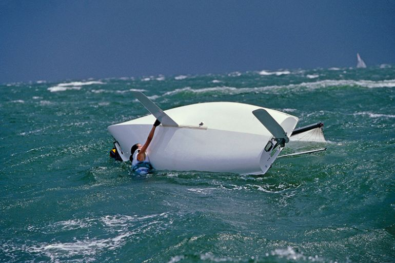 Capsized woman and boat