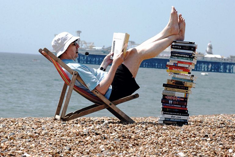 Man on beach reading