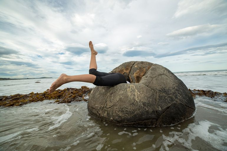 Woman falling into rock on beach