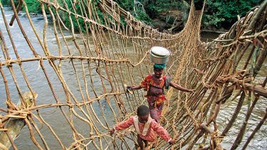 African woman and child crossing rope bridge