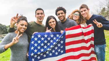 American students posing with USA stars and stripes flag