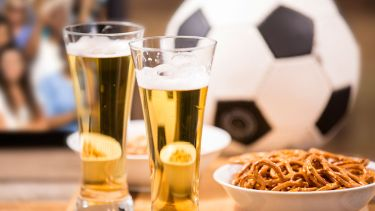 Beer, pretzels and football on pub table