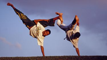 Brazilian men performing capoeira outdoors