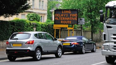 Cars in traffic jam with 'Long delays, find alternative route' sign