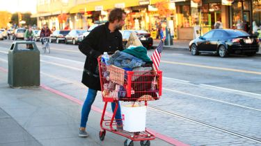 Homeless man pushing shopping cart full of belongings