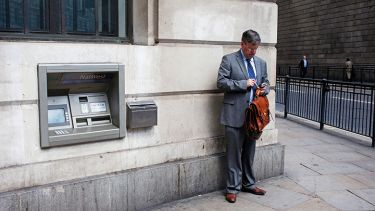 Man standing next to cash machine