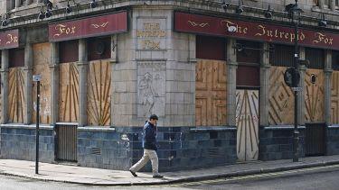 Man walks past a vacant building
