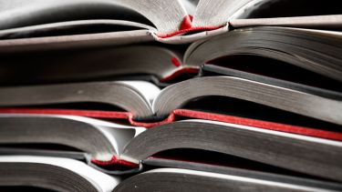 Collection of bound essays piled high