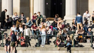 Crowd of University College London (UCL) students relaxing in sunshine