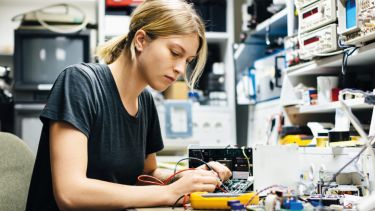 Female engineer measuring voltage on conductor board