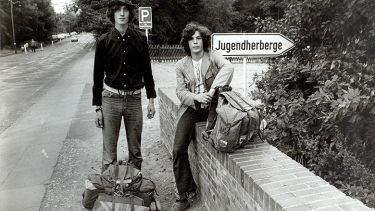 Two young men heading to a festival
