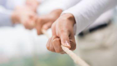 Hands pulling rope, tug of war, teamwork
