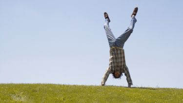 Student handstand on grass