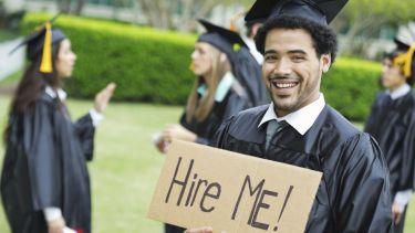 Graduate holding hire me sign