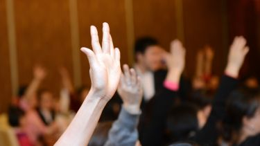 Students putting hands up in lecture theatre
