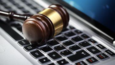 Judge's gavel on computer keyboard