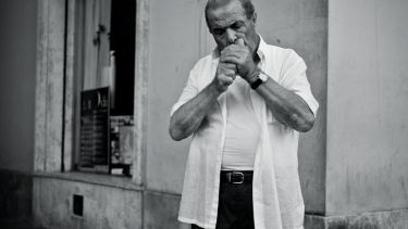 Italian man cupping hands to light cigarette
