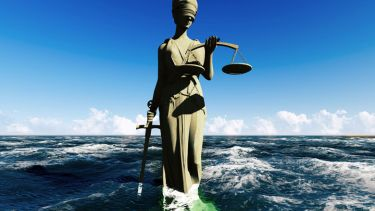 Lady Justice statue sinking into sea water